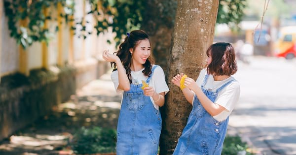 Matching outfit Instagram captions, two Asian stand next to a tree, both wearing denim overall dresses and white t-shirts, fashion