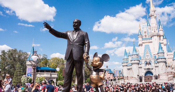 Walt Disney holding Mickey Mouse hand statue with Magic Kingdom castle behind, Disney Theme Park ranking
