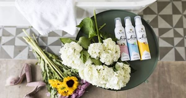 Olay skincare products and flowers with towel and bathtub, best skincare brands