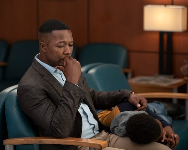 man sitting looking down with hand on face and boy in lap, Grey's Anatomy season 15
