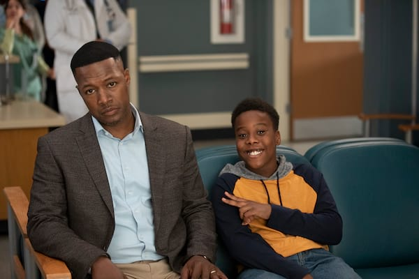 man and son sitting in chairs looking forward son is smiling and throwing a peace sign, Grey's Anatomy via ABC