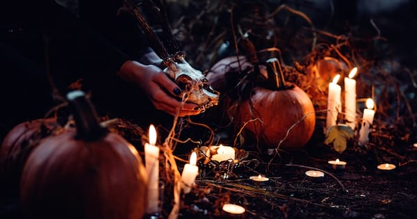 Spooky Instagram Captions, two hands cradling an animal skull in the woods, surrounded by candles and pumpkins, culture