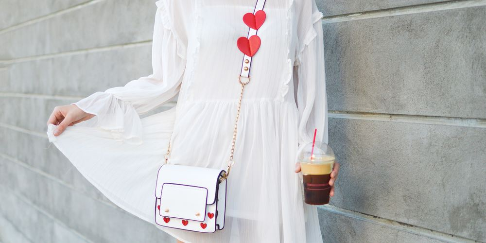 Woman wearing a white dress with red heart accessories, dress Instagram captions, fashion