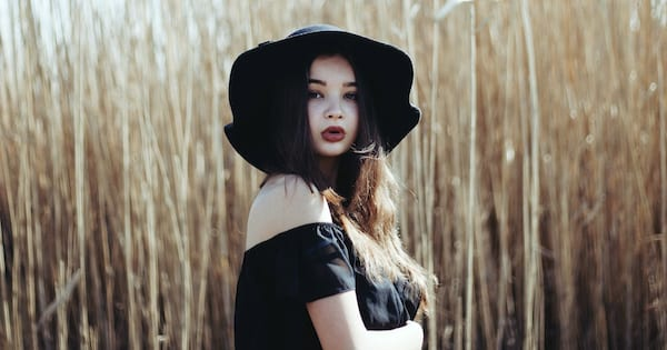 Ultimate Witchy Halloween Playlist, woman of undetermined ethnicity wearing a black hat and shirt standing before a field, Music