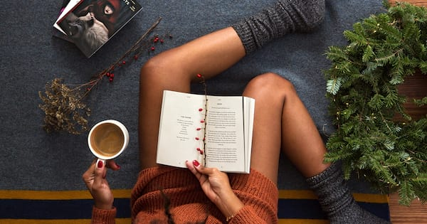 Ways to practice self care during mental health awareness week, photo of a black woman wearing a brown sweater, drinking coffee and reading a book, health