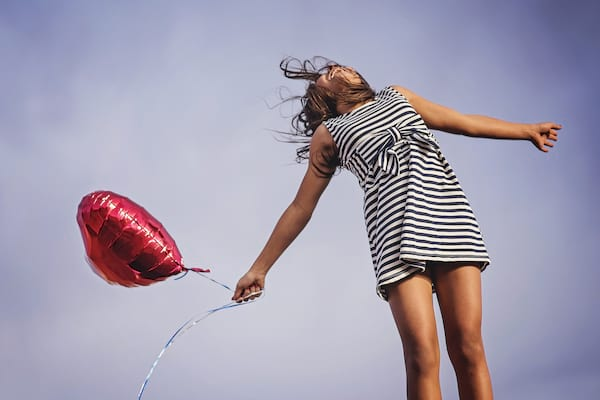 Woman jumping with heart balloon.
