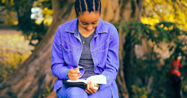health, books, a black woman wearing a denim shirt and pants reads a book outside, Books to read if you've recently been diagnosed with a chronic illness