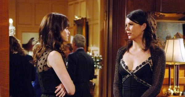 Lorelei and Rory in black dresses standing looking at each other on Gilmore Girls, tv entertainment Halloween