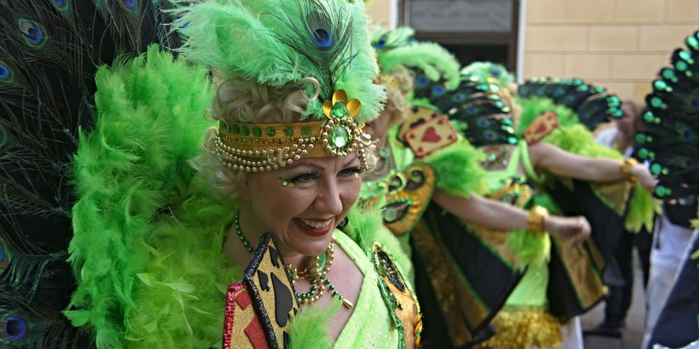 Woman dressed in a green Mardi Gras costume in a parade, New Orleans Instagram captions, culture, travel