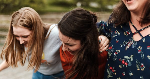 Small ways to support the chronically people in your life, three white women with their arms around each other smiling and laughing together, health, relationships