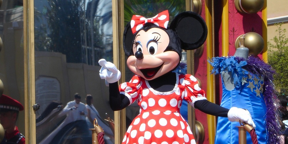 Minnie Mouse in costume at a Disney World park riding on a float and pointing, movies