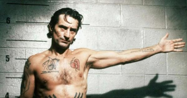 Cape Fear star standing in jail cell shirtless with arm out, movie
