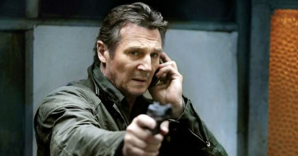 Bryan Mills holds cell phone to ear and points gun, movie