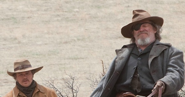True Grit U.S. Marshal sitting in desert wearing hat and eye patch, movie