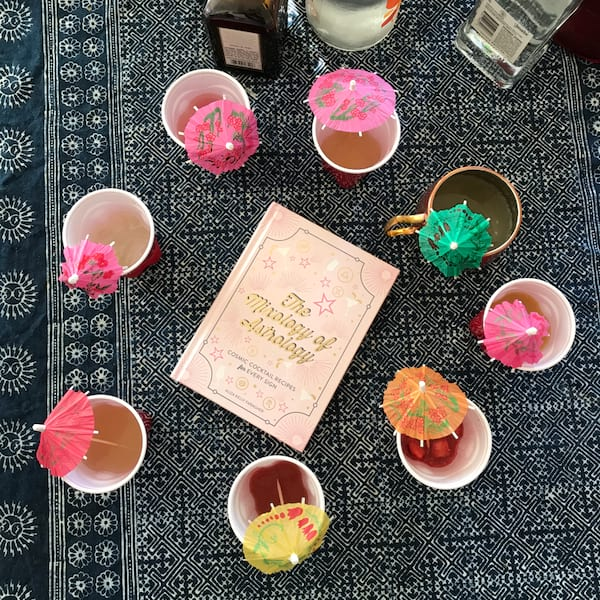 A mix of cocktails circled around Aliza Kelly Faragher's 'The Mixology of Astrology' cocktail recipe book