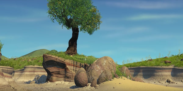 A single tree standing on top of a hill surrounded by grass and rocks and sand in Pixar's A Bug's Life, movies