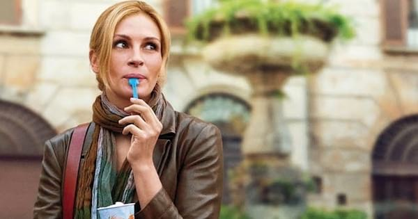 Liz Gilbert (Julia Roberts) standing outside with ice cream spoon in mouth, movies rank