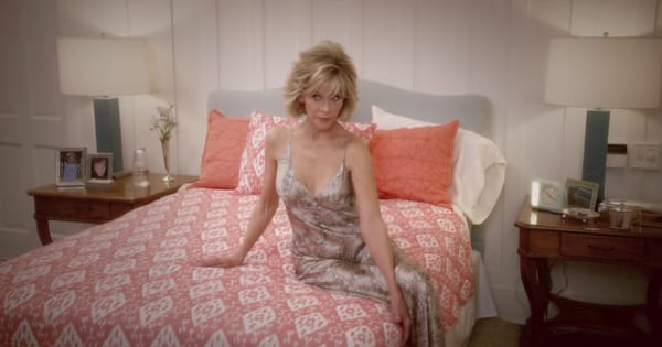 Jane Fonda sitting seductively on her bed while wearing a sultry night gown