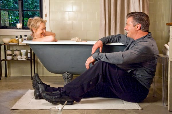 Meryl Streep sitting in a bathtub while Alex Baldwin sits outside of it in the movie It's Complicated