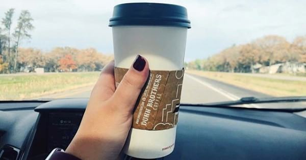 woman's hand holding coffee in car, ranking