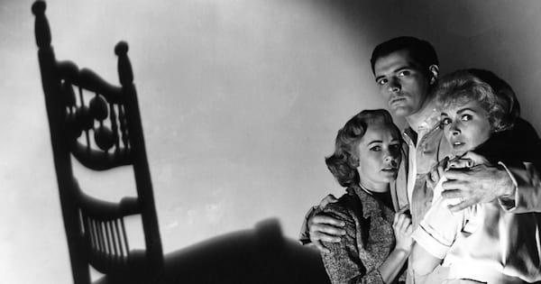 woman and two men huddled together in fear, movies horror ranking