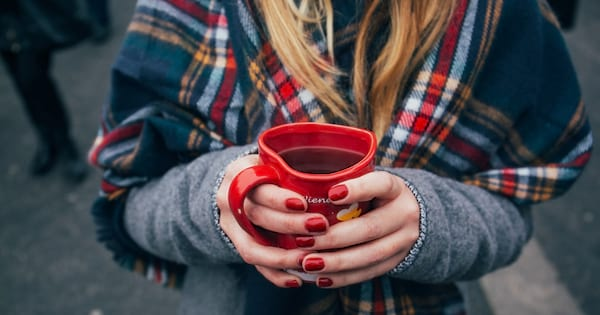 The Best Teas To Drink If You Get Seasonal Depression, closeup of a white woman's hands holding a red mug of tea, health, food & drinks