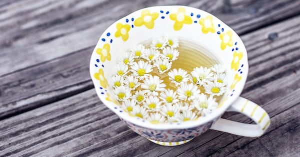 The Best Teas To Drink For Seasonal Depression, closeup of a teacup full of chamomile flowers, health, food & drinks