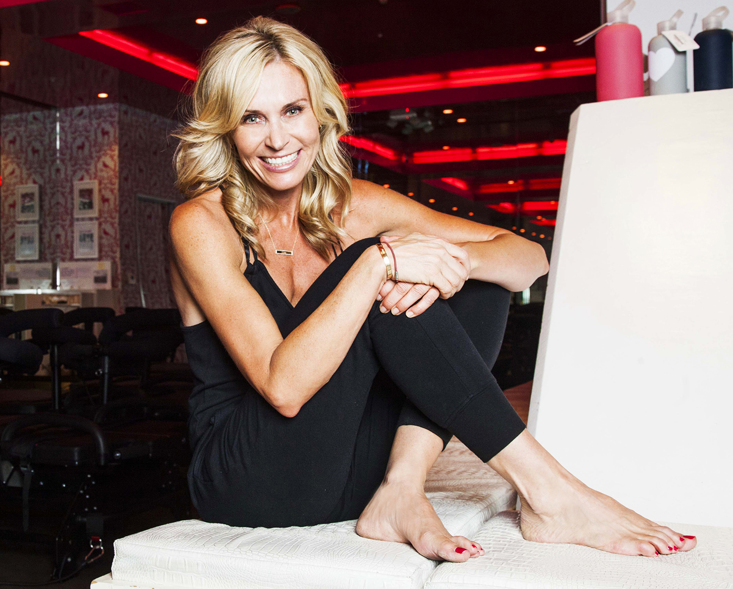 Lisa Hirsch-Solomon sitting on a white couch wearing all black workout gear