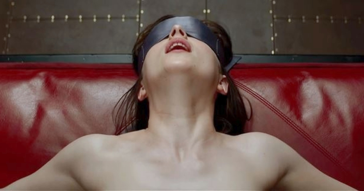 Dakota Johnson as Ana wearing a blindfold and sitting on a couch in Fifty Shades of Grey (2015)