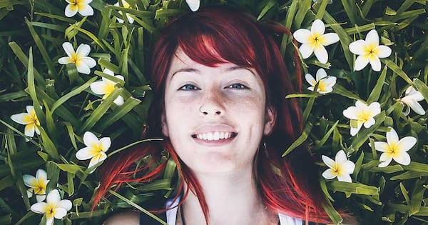 Taurus Instagram Captions, closeup of a white woman with red hair smiling and lying in the grass
