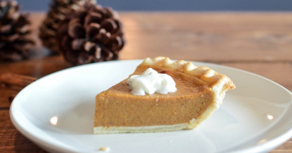 slice of pumpkin pie with cool whip on plate, thanksgiving
