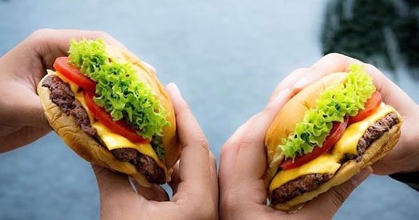 two hands holding burgers up next to each other from shake shack, food