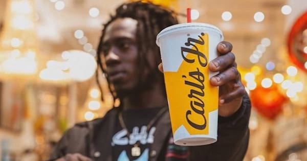 man holding carl's jr. cup, food