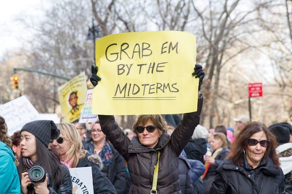 female protestor holding a yellow poster that reads \grab them by the midterms\