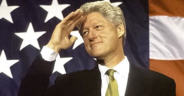 president bill clinton saluting in front of a flag