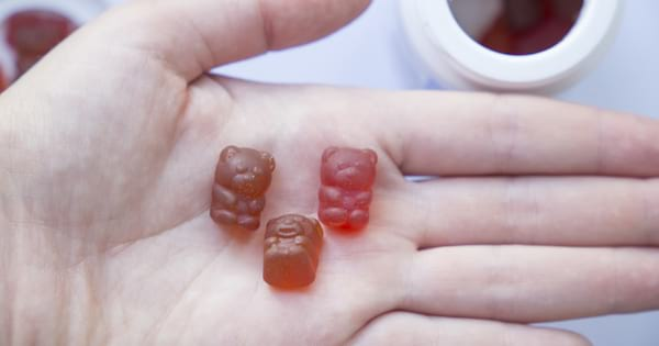 Person holding three bear gummy vitamins in their hand