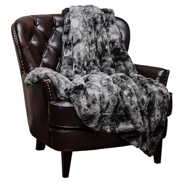 Faux fur throw blanket draped over a leather arm chair