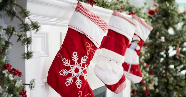 Three Christmas stockings hanging over a white fireplace