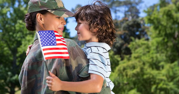 Woman dressed in military wear holding her son in her arms