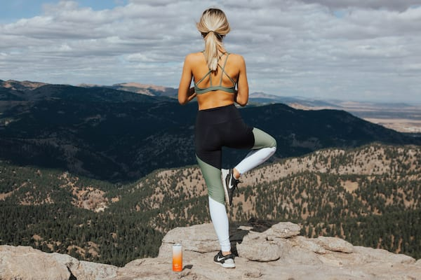 Girl doing yoga on a mountain with a can of Gac right next to her
