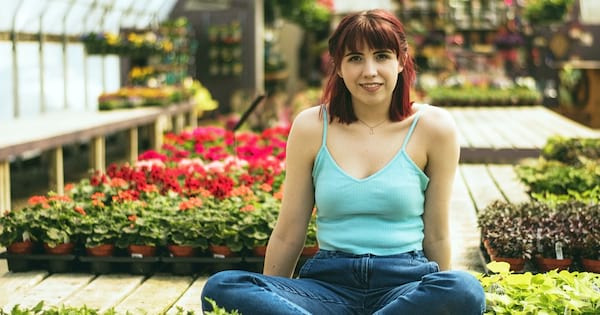 Garden Instagram Captions, a white woman with red hair sits in a greenhouse surrounded by plants