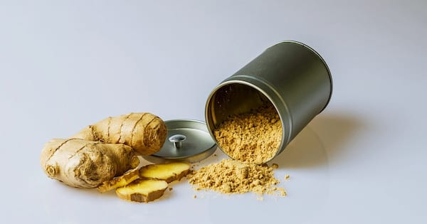 Benefits of Ginger, photo of ginger root and ground ginger tumbling out of a container set to a white background, health, food & drinks