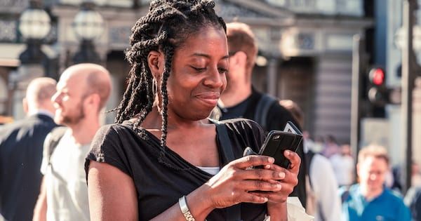Health Apps That Help Track Your Symptoms, closeup of a black woman with her hair in braids and wearing a black shirt looking down at her cell phone, health