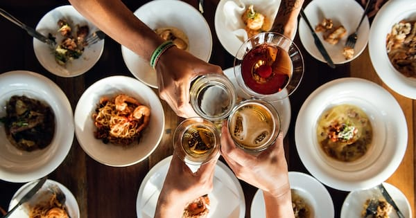 Dinner Party Instagram Captions, photo of several people clinking their glasses together, food & drinks