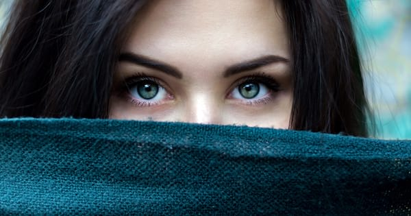 Instagram Captions For Green Eyes, closeup of a white woman with green eyes and dark hair, beauty