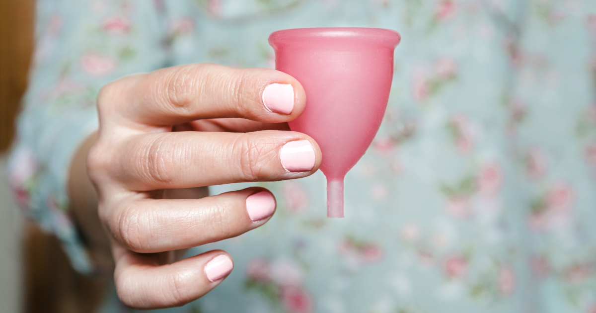 Woman holding a pink menstrual cup in her hand