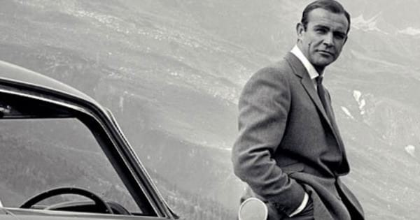 black and white james bond leaning on car