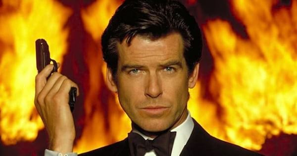james bond holding gun in front of fire