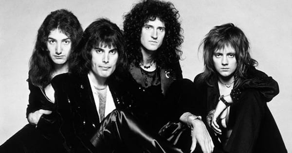 queen band members sitting down covered in black