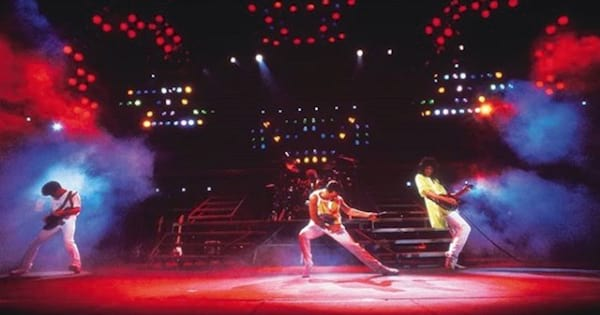 queen band on stage performing during their magic tour